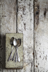 Overhead view of spoons and metallic container on wooden table