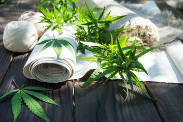 Leaves of cannabis and hemp cloth rollon the dark wooden surface