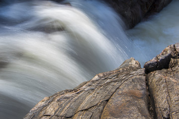 fast moving, blurred waterfall with large rock in foreground