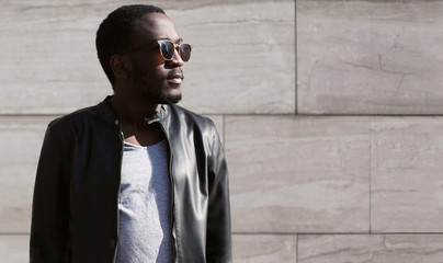 Fashion young african man wearing a sunglasses and black rock le