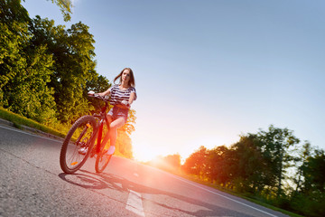 girl on a bicycle at sunset