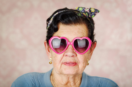 Older cool hispanic woman wearing blue sweater, flower pattern bow on head and pink heartshaped sunglasses looking into camera