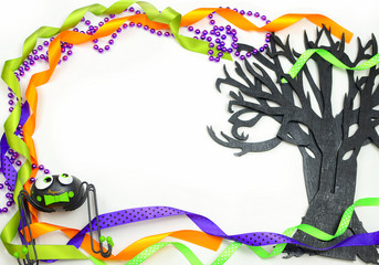 Halloween border of a rough textured wooden cutout of bare tree shape painted black. A silly spider and purple, green and orange ribbons and beads frame the copy space on white background