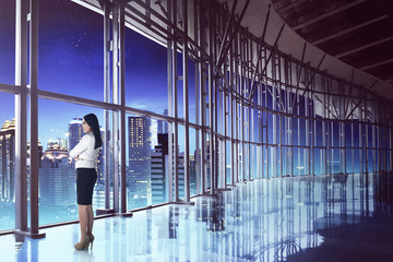 Asian business woman looking the city at night