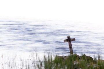 Wooden cross standing on the shore with streaming water