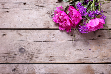 Spring pink peonies flowers on aged wooden background.