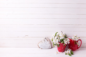 Background with apple tree flowers and heart  on white wooden pl