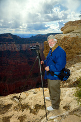 Senior Man Stands on the North Rim of the Grand Canyon Taking Pi