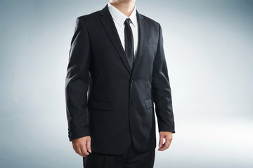 close up part of man body in black suit on white background; business concept