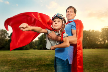 Father and son playing in superhero costumes in the park on natu