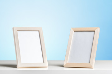blank white picture frame on the wall and the table wood