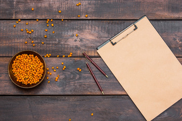 Office desk table with notebook, fresh buckthorn berries on wooden table