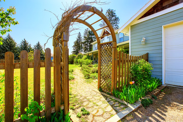 View of Wooden arbor. Arched entry to the garden.