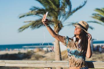 Brunette woman makes selfie on the beach