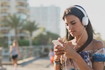 Brunette woman listening music on smartphone