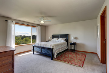 Bedroom interior with beige walls, rug and white curtains