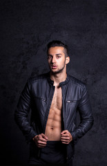 Sexy and expressive shirtless male model flirting against black
