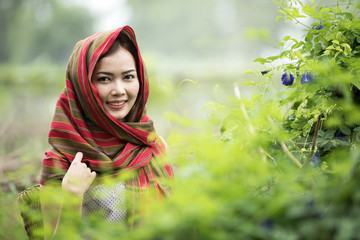 Portrait of beautiful young Thai woman farmer choosing green