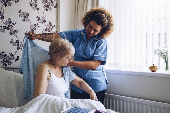 Home caregiver dressing senior