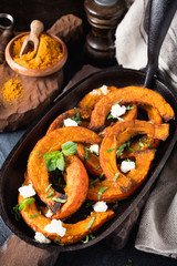 Spicy roasted pumpkin with goat cheese and mint on a cast iron skillet. Healthy food concept.