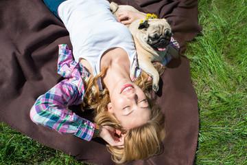 девушка с собакой лежат на траве под солнцем
