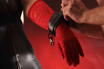 Lederfesseln auf roten Handschuhen anlegen