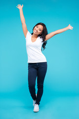 Cheerful young asian woman standing with raised up hands