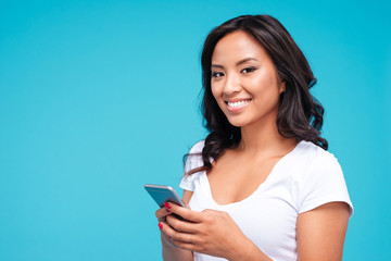 Portrait of a smiling casual asian woman holding smartphone