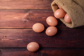 eggs in sackcloth bag on wooden background