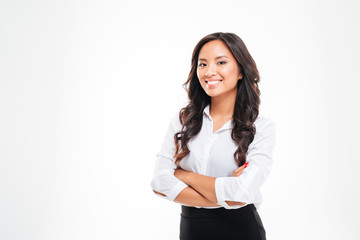 Smiling pretty young asian businesswoman standing with arms crossed