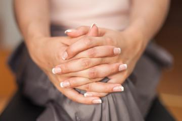 Frau überkreuzt Hände auf Knie
