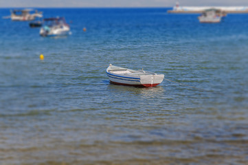 Old fishing white and blue boat tied on shore