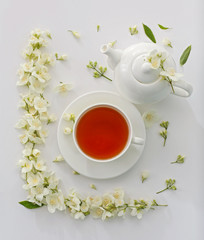 Cup of tea with jasmine flowers on white background