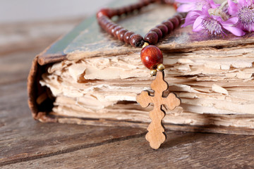 Wooden cross with flowers and old book, closeup
