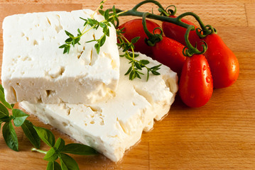 Feta cheese served with fresh tomatos, basil and thyme on wood board