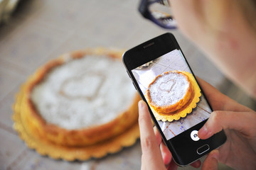 Girl photographs a cake with her smartphone