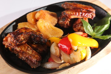 metal pan with chicken wings and vegetables