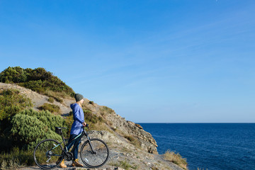 attractive young smiling blonde woman with the bike is standing on a rock and looking at the sea