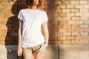 Young girl in a white blank t-shirt and shorts is standing on a brick wall background on a sunny...