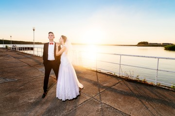 Bride and groom on the pier at sunset.