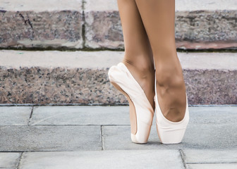 Feet dressed in dance pointe shoes, sports shoes on the background of stone steps. Sexy female legs.