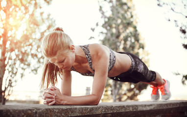 Athletic woman standing in plank position outdoors at sunset. Concept of sport, recreation and motivation.