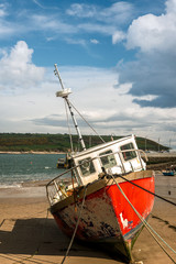 Red fishing boat during low tide at Youghal port