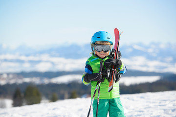 Happy skier boy in the mountains during winter holiday