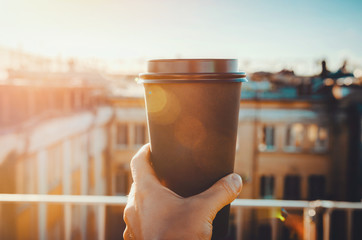 hands holding hot craft cup of coffee or tea in morning sunlight with view to blurred city background. Enjoy, lifestyle, take away breakfast concept. woman on the roof with hot drink