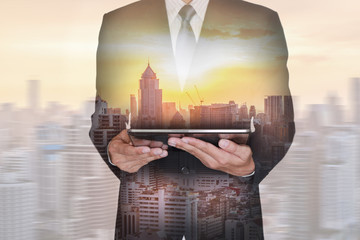 Double exposure of business man hand hold tablet, city and sunset as technology concept.