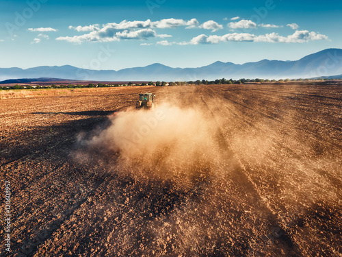 Wall mural Tractor cultivating field at autumn