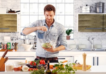 Handsome man preparing salad in kitchen