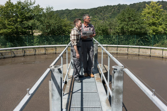 Two engineers standing on bridge over sedimentation tank monitoring the wastewater treatment with tablet computer
