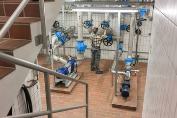 Technician opening valve in pipe system of wastewater treatment plant